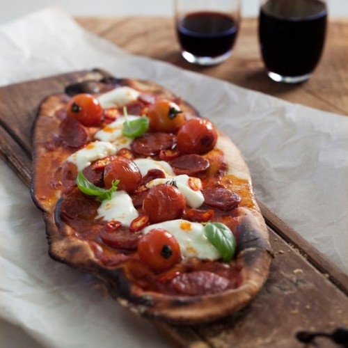 Homemade Pizza Served On A Wooden Slab
