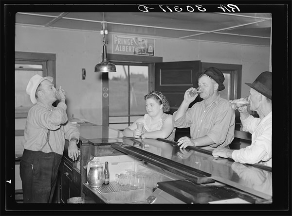 A drink on the house. Lumberjacks, proprietor and lady attendant in saloon