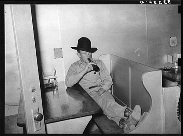 Cowboy drinking a bottle of beer in booth of beer parlor