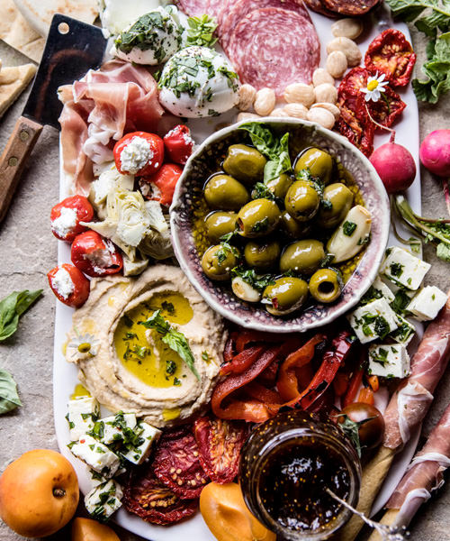We're Obsessed With These 15 Swoon-Worthy Cheese & Charcuterie Boards Mediterranean Stuffed Tomatoes Olives Hummus Feta Mozzarella